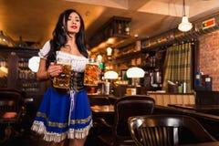 Bella cameriera di bar femminile che porta dirndl tradizionale e che tiene le birre enormi in un pub immagine stock
