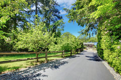 Bella casa con i portoni privati, la strada privata lunga ed il giardino. Fotografia Stock