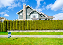 Bella casa dietro un recinto verde della barriera Fotografie Stock