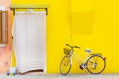 Bella casa gialla con una bicicletta Case variopinte nell'isola di Burano vicino a Venezia, Italia Fotografia Stock