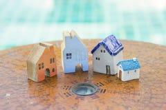 Bella casa miniatura sulla bussola di legno antica di feng shui sopra il fondo vago dell'acqua blu Fotografia Stock