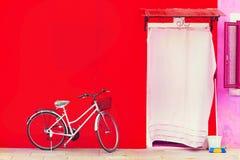 Bella casa rossa con una bicicletta Le case variopinte in Burano è Fotografia Stock Libera da Diritti