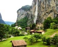 Bella cascata di Staubbachfall che entra giù la valle di Lauterbrunnen ed il villaggio pittoreschi nel cantone di Berna, Svizzera Fotografia Stock