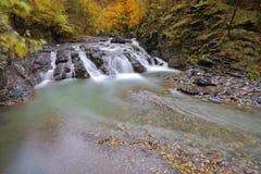 Bella cascata in foresta, paesaggio di autunno con i lotti di rosso Fotografia Stock Libera da Diritti