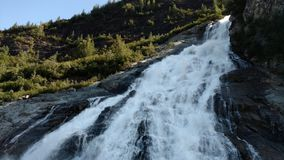Bella cascata lungo il ghiacciaio laterale di Mendenhall a Juneau Alaska Grande ghiacciaio che si infila in un lago con una casca fotografia stock libera da diritti
