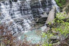 Bella cascata precipitante a cascata che circola sulle rocce a file nello swi immagine stock libera da diritti