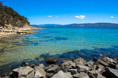 Bella chiara acqua sulla costa di una spiaggia Immagini Stock Libere da Diritti