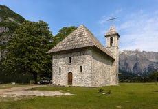 Bella chiesa dell'pietra-e-assicella di Theth nelle alpi albanesi, un punto culminante turistico in Albania del Nord Immagine Stock