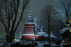 Bella chiesa di legno illuminata nell'inverno in pieno di neve Tylicz Polonia fotografie stock