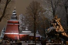 Bella chiesa di legno illuminata nell'inverno in pieno di neve Tylicz Polonia fotografia stock libera da diritti