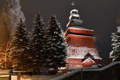 Bella chiesa di legno illuminata nell'inverno in pieno di neve Tylicz Polonia fotografia stock