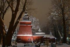 Bella chiesa di legno illuminata nell'inverno in pieno di neve Tylicz Polonia fotografie stock libere da diritti