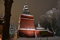 Bella chiesa di legno illuminata nell'inverno in pieno di neve Tylicz Polonia immagine stock
