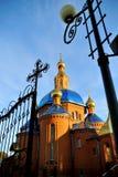 Bella chiesa ortodossa del mattone rosso con un tetto blu, con le cupole dorate al tramonto La Russia, Belgorod Aspetto generale Fotografia Stock
