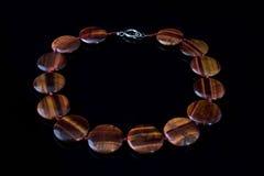 Bella, collana elegante fatta dell'occhio di pietra della tigre su un fondo nero Immagini Stock