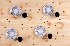 Bella composizione astratta nel caffè Tazze e piattini della porcellana con i chicchi di caffè sparsi su un fondo di legno Fotografia Stock