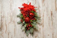 Bella composizione in Natale per la decorazione della porta fatta dell'albero di abete e delle palle rosse Fotografia Stock Libera da Diritti