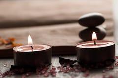Bella composizione nella stazione termale con le candele dell'aroma e libro aperto d'annata vuoto su fondo di legno Fotografia Stock