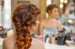 Bella, con lungamente, la ragazza pelosa dai capelli rossi, parrucchiere tesse una treccia francese, in un salone di bellezza fotografie stock