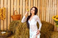 Bella condizione castana snella in vestito bianco in granaio con il hayloft, concetto di rilassamento fotografia stock