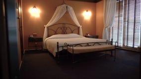 Bella condizione del letto matrimoniale in una piccola camera di albergo accogliente la macchina fotografica si muove da sinistra archivi video