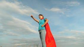 bella condizione del supereroe della ragazza sul campo in mantello rosso, mantello che fluttua in vento Movimento lento Primo pia video d archivio