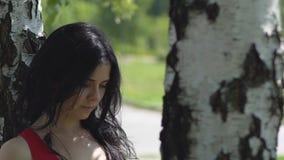 Bella condizione mora sola della donna triste sotto l'albero di betulla all'aperto lento video d archivio