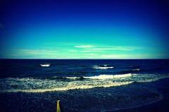 Bella costa pulita del mare blu senza fine verso il sole luminoso Fotografia Stock