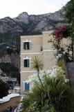 Bella costruzione su un fondo delle montagne Circondato dai fiori Immagini Stock