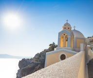 Bella cupola gialla della chiesa sull'orlo della città di Fira Immagine Stock