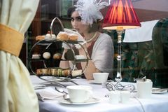 Bella donna in abbigliamento d'annata che gode del tè di pomeriggio in trasporto del treno immagini stock libere da diritti