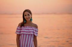 Bella donna abbronzata in vestito con le bande bianche e rosa Chiuda su e copi lo spazio Mare o oceano arancio al tramonto vacanz immagini stock libere da diritti