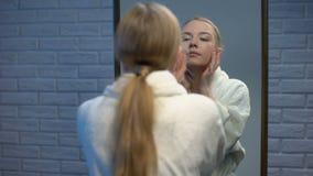 Bella donna in accappatoio che applica la crema di fronte d'idratazione, bellezza naturale archivi video