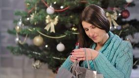 Bella donna accogliente pacchetto e sorridere d'apertura del regalo di poco Natale video d archivio