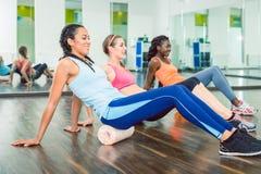 Bella donna adatta che si esercita sul rullo della schiuma durante la classe di allenamento del gruppo Immagine Stock Libera da Diritti