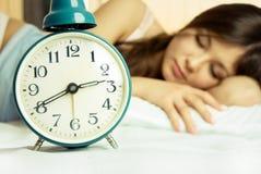 Bella donna addormentata con una sveglia Immagine Stock