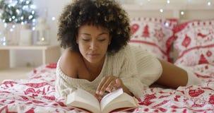 Bella donna africana calma che legge a letto video d archivio