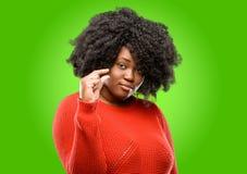 Bella donna africana con capelli ricci isolati sopra fondo verde immagini stock