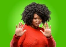 Bella donna africana con capelli ricci isolati sopra fondo verde immagine stock