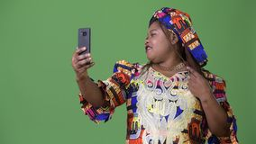Bella donna africana di peso eccessivo che indossa abbigliamento tradizionale contro il fondo verde stock footage