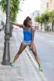 Bella donna africana di sport che fa gli allungamenti, stile di vita sano immagine stock