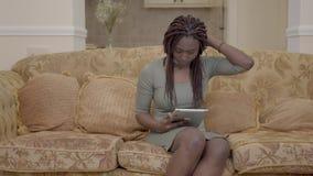 Bella donna afroamericana che si siede nel salone sulla vettura e che cerca qualcosa sulla compressa video d archivio