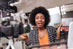 Bella donna afroamericana dalla carnagione scura con capelli ricci che sembrano eccitati immagine stock libera da diritti