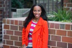 Bella donna afroamericana felice che porta rivestimento rosso che sta e che sorride alla città universitaria dell'istituto univer Fotografia Stock Libera da Diritti