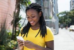 Bella donna afroamericana in un messa mandante un sms della camicia gialla Fotografia Stock Libera da Diritti