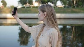 Bella donna alla moda che fa selfie sui precedenti del fiume archivi video