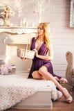 Bella donna alla moda che si siede nell'interno della stanza bianca con il canestro fotografia stock