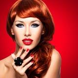 Bella donna alla moda con le unghie rosse ed i capelli rossi fotografia stock libera da diritti