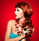 Bella donna alla moda con le unghie rosse ed i capelli rossi fotografia stock