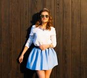 Bella donna alla moda in occhiali da sole, una minigonna blu che posa vicino alla parete di legno di una sera calda di estate Fotografie Stock